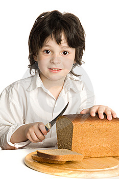 The Liitle Boy Wich Slicing A Bread On Desk Royalty Free Stock Photo - Image: 10059605