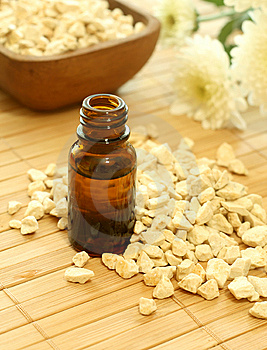 Bottle Of Essence Oil With Flowers And Stones Royalty Free Stock Photos - Image: 10093908