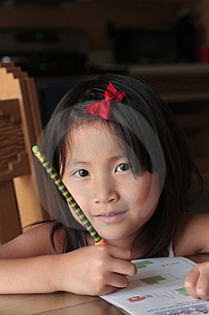 smiling asian girl doing homework Stock Images