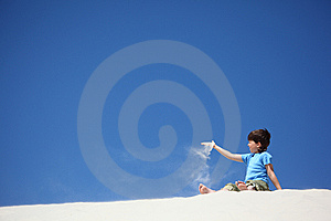 Boy Sits On Sand And Scatters It Royalty Free Stock Photography - Image: 10354187