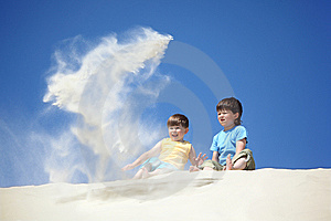 Two Boys Sit On Sand And Scatter It Royalty Free Stock Images - Image: 10354209