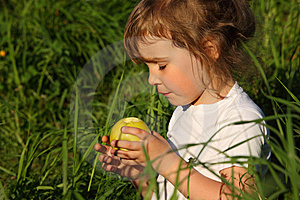 Girl In Grass With Green Apple Stock Photos - Image: 10354853