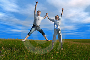 Jumping couple in field under clouds Stock Photography