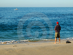 Man Surf Fishing on  Blue Blue Ocean