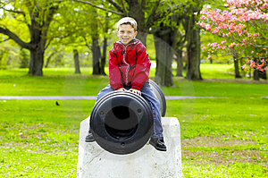 Child Sitting On Cannon Stock Photo