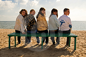 Group of five smiling young people on a bench Royalty Free Stock Photos