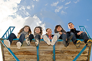 Company of five young people sitting together Royalty Free Stock Photo