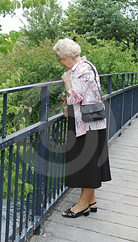 Senior lady looking into river Royalty Free Stock Photo