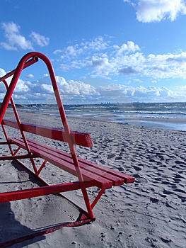 Banco rojo en la playa Imágenes de archivo libres de regalías