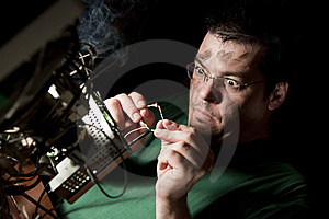 Man repairing computer on fire Free Stock Image