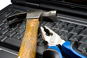 Hammer and pliers on a laptop