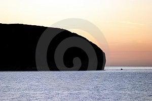 Petit bateau entrant dans une baie au lever de soleil Images libres de droits