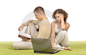 Young couple on green carpet with laptop and book