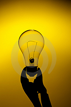 A Light Bulb Held In A Grip On A Yellow Gl Stock Photo - Image: 13559330