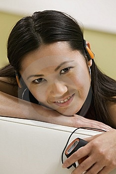 Young Woman Lying On Sofa Listening To Music Royalty Free Stock Image - Image: 13584376