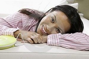 Woman Lying On Sofa Listening To Music Royalty Free Stock Photo - Image: 13584395
