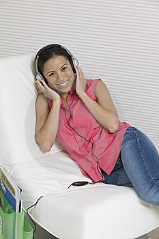 Woman Reclining On Chair Listening To Music Royalty Free Stock Photos - Image: 13584398