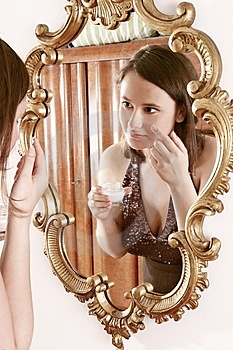 Woman putting cream in front of  a mirror