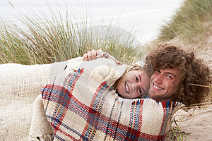 Teenage Couple Sitting In Sand Dunes Wrapped In Bl Stock Photos - Image: 13672273