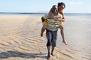 Young Man Giving Woman Piggyback Along Shoreline Royalty Free Stock Photography - Image: 13673337