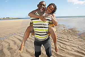 Young Man Giving Woman Piggyback Along Shoreline Royalty Free Stock Photography - Image: 13673357