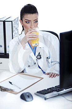 Doctor Drinking A Glass Of Juice At Her Workplace Royalty Free Stock Image - Image: 13715546