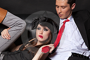 Young Glamourous  Couple On Black Sofa. Stock Photos - Image: 13796943