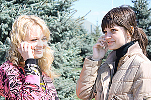 Two Girls Call By Phone In A Park Royalty Free Stock Image - Image: 13833526