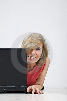 Happy Mature Woman With Laptop On Wooden Floor Royalty Free Stock Images - Image: 13938999