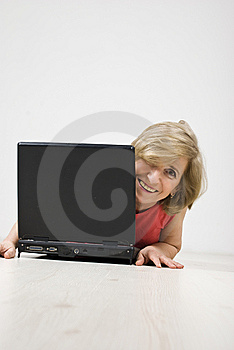 Senior Woman Laughing Behind A Laptop Royalty Free Stock Images - Image: 13966989