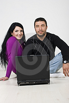 Couple Using Laptop On Wooden Floor Stock Images - Image: 13993354