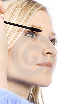 Closeup of young woman's face putting mascara Stock Photos