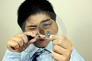 A Boy Examining A Coin Royalty Free Stock Photography - Image: 14164927