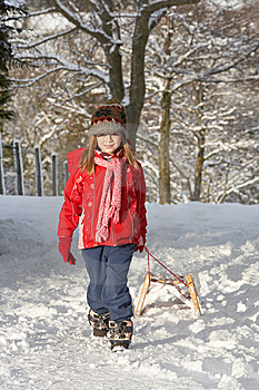 Young Girl Pulling Sledge Through Snowy Landscape Stock Images - Image: 14189024