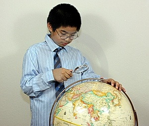 A Boy Examining A Globe Royalty Free Stock Photography - Image: 14285037