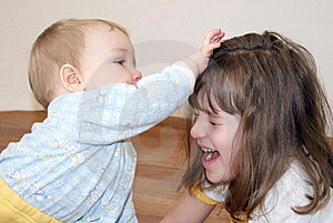 The Girl Plays With The Brother Stock Image - Image: 14321771
