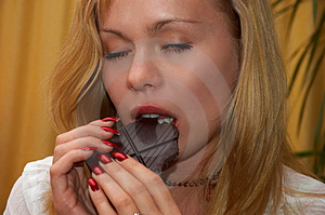Pretty Blonde Girl Eating Chocolate Stock Image - Image: 1449501