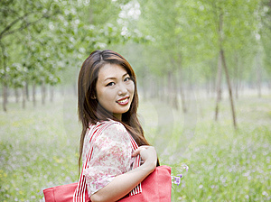 Cheerful Asian Woman Carrying Shopping Bag Royalty Free Stock Images - Image: 14569679