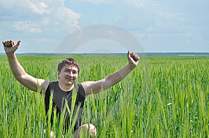 A Man Sits In A Field Of Green Wheat Stock Photography - Image: 14577012