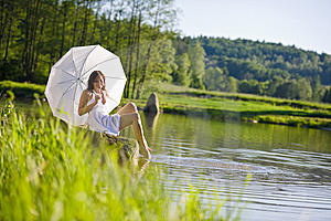 Spring - Happy romantic woman sitting by lake