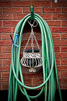 Coiled Garden Hose Hanging On Brick Wal Stock Images - Image: 14700734