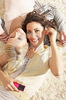 Two Women Listening To MP3 Player On Headphones Royalty Free Stock Photos - Image: 14726138