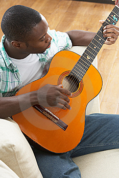 Man Relaxing Sitting On Sofa Playing Guitar Royalty Free Stock Image - Image: 14730936