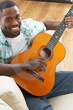 Man Relaxing Sitting On Sofa Playing Guitar Stock Image - Image: 14731001