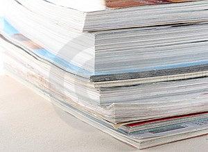 Pila di riviste colorate su sfondo bianco.