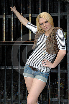Blond Girl Posing Against Metal Gate Royalty Free Stock Images - Image: 14858529