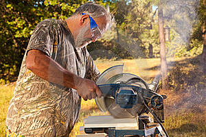 Senior Man Operating A Chop Saw Royalty Free Stock Photo - Image: 14923915