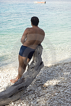 Man Leang On Tree On A Pebbly Beach In Paxos Greec Royalty Free Stock Image - Image: 15030986
