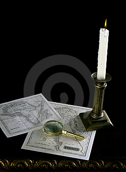 A Candle With Old Maps And Magnifying Glass Stock Photo - Image: 15141280