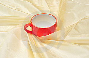 Red Cup At The Golden Fabric Drapery Royalty Free Stock Photo - Image: 15281075